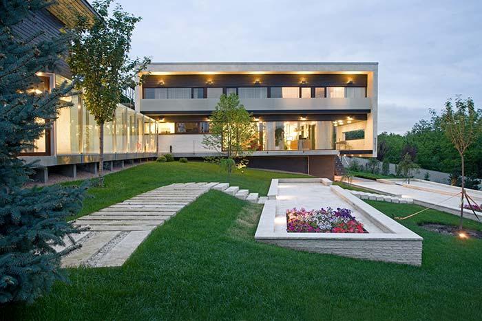 A iluminação da fachada da casa se completa com a iluminação do jardim