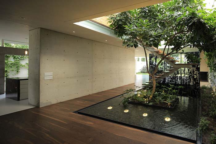 Jardim interno com árvore e lago ficou mais sofisticado com as luzes sob a água