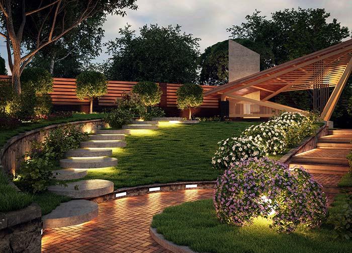 Nesse jardim, a iluminação fica escondida debaixo da escada e dentro dos arbustos floridos