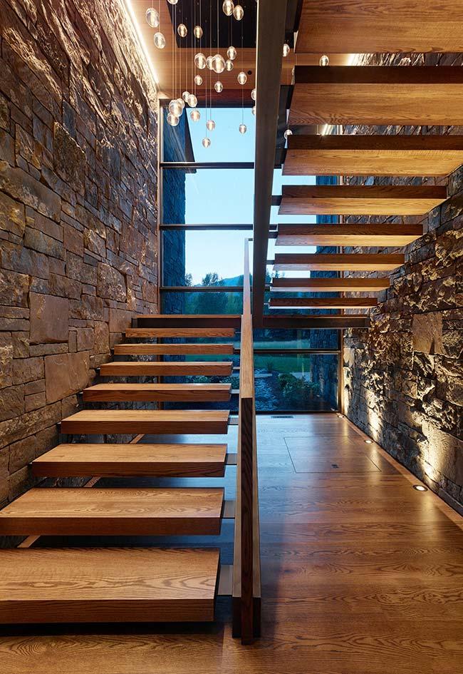 As pedras brutas em conjunto com a madeira deixam a entrada da casa com aspecto rústico e bem acolhedor