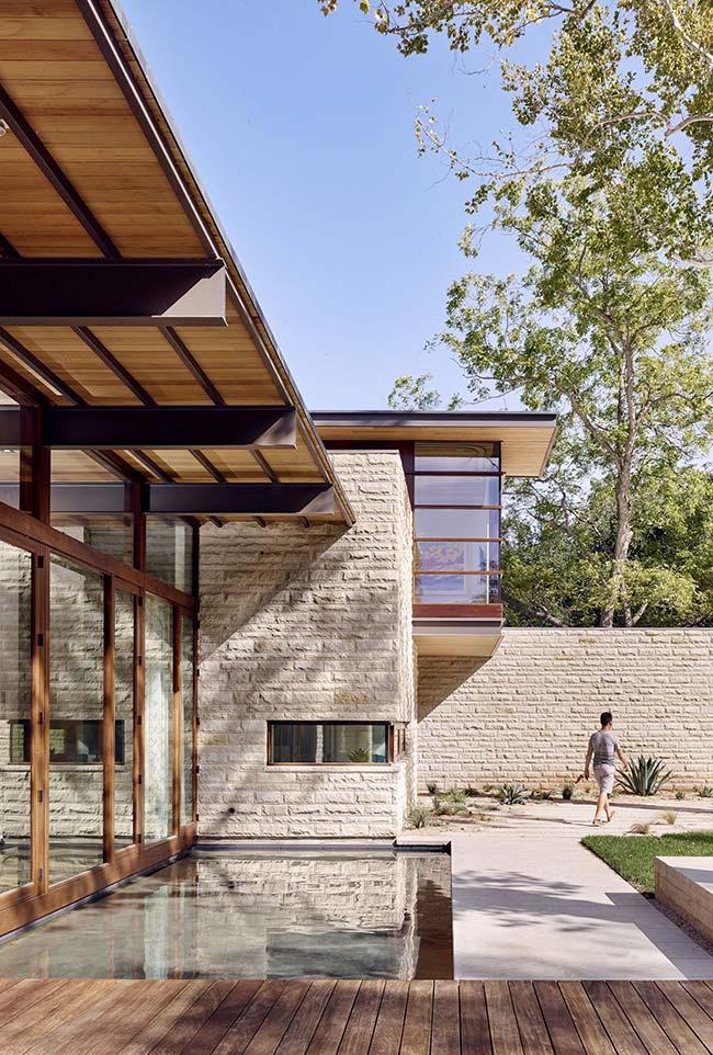 A fachada dessa casa moderna foi revestida apenas com elementos rústicos: madeira e pedra miracema