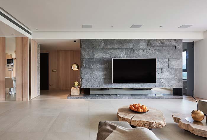 Sala de decoração clean e elegante contou com a beleza bruta das miracemas na parede atrás da TV