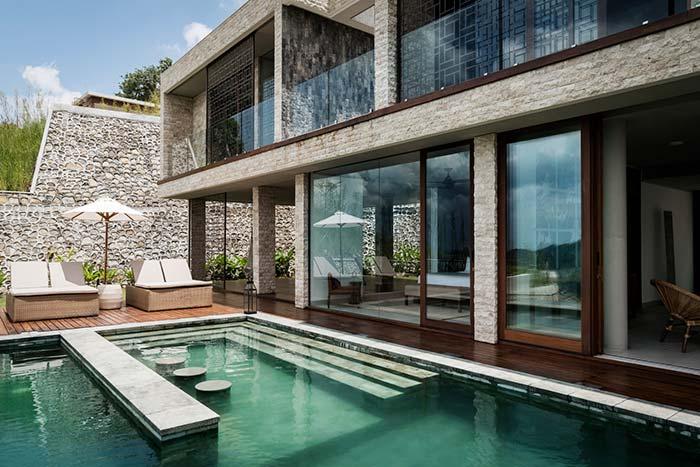 Área externa, perto da piscina, ganhou piso de madeira e paredes revestidas com Miracema branca
