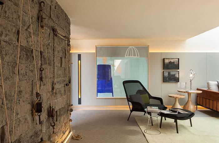A parede bruta e rústica com objetos decorativos inusitados contrastam com a sala de decoração clean e suave
