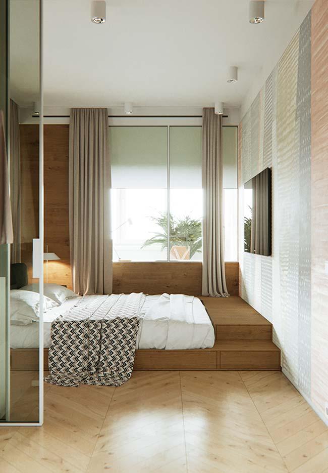 Nesse quarto, a base de madeira serve de encaixe para a cama e de passagem até a janela e a TV