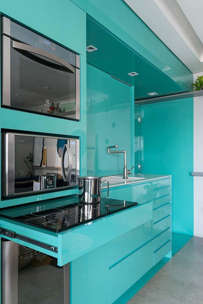 Nessa cozinha azul toda laqueada, o cooktop de indução fica guardadinho no armário depois do uso