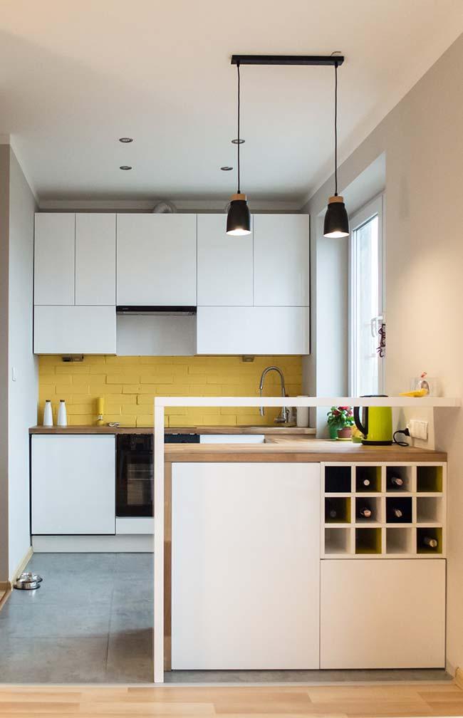 A cozinha toda branca ganhou um toque de vida e descontração com a parede de tijolinhos pintada de amarelo