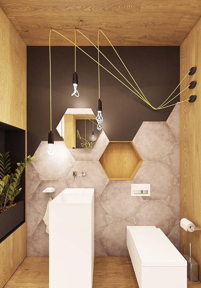 O preto na parede desse banheiro foi suavizado com a presença dos elementos em madeira e da iluminação amarelada