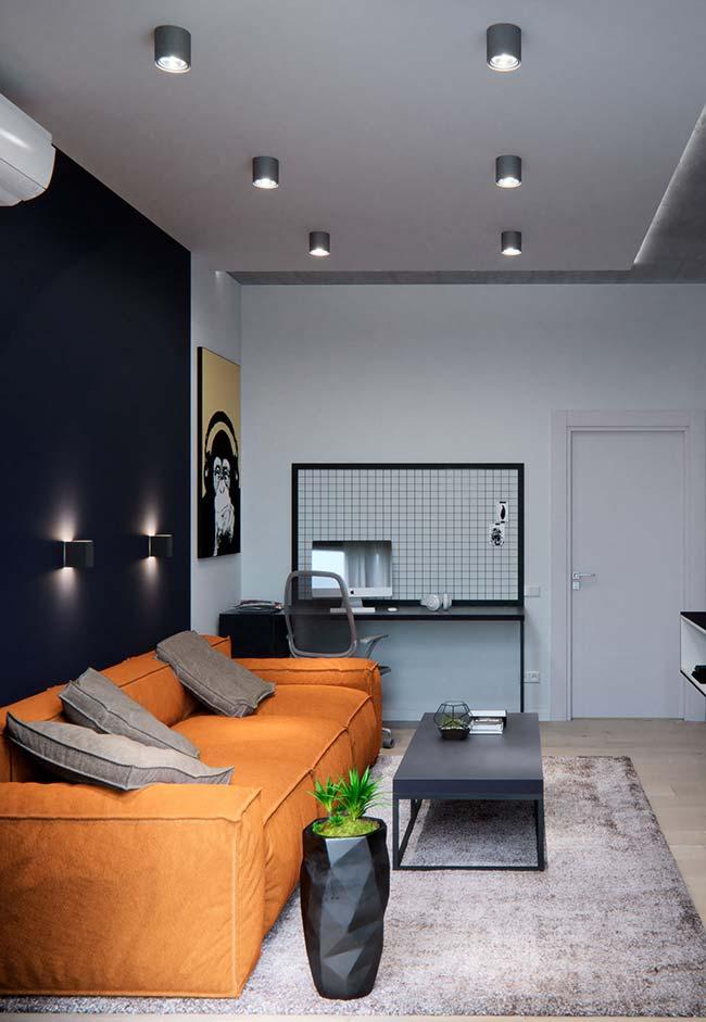 Nessa sala, a parede preta foi contrastada com o sofá laranja; uma combinação e tanto