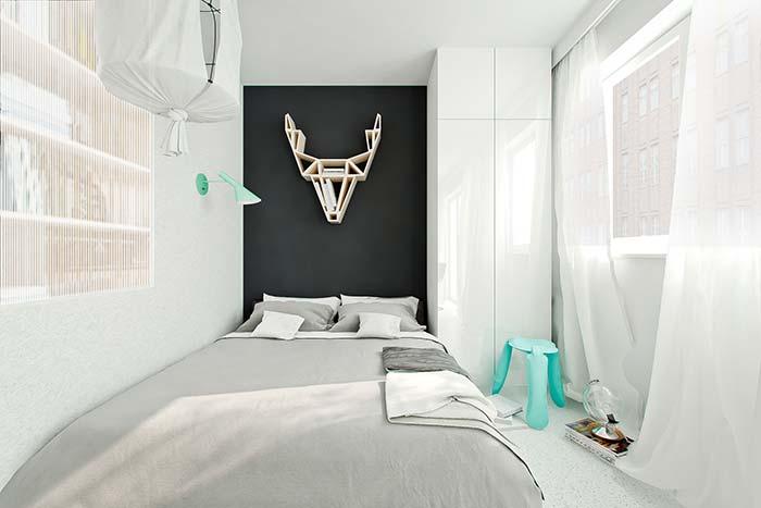 Essa decoração moderna e minimalista apostou em uma faixa de parede preta para criar contraste