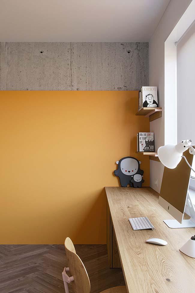 Moderno e descontraído: a parede de tom amarelo amêndoa divide espaço com a faixa de concreto aparente