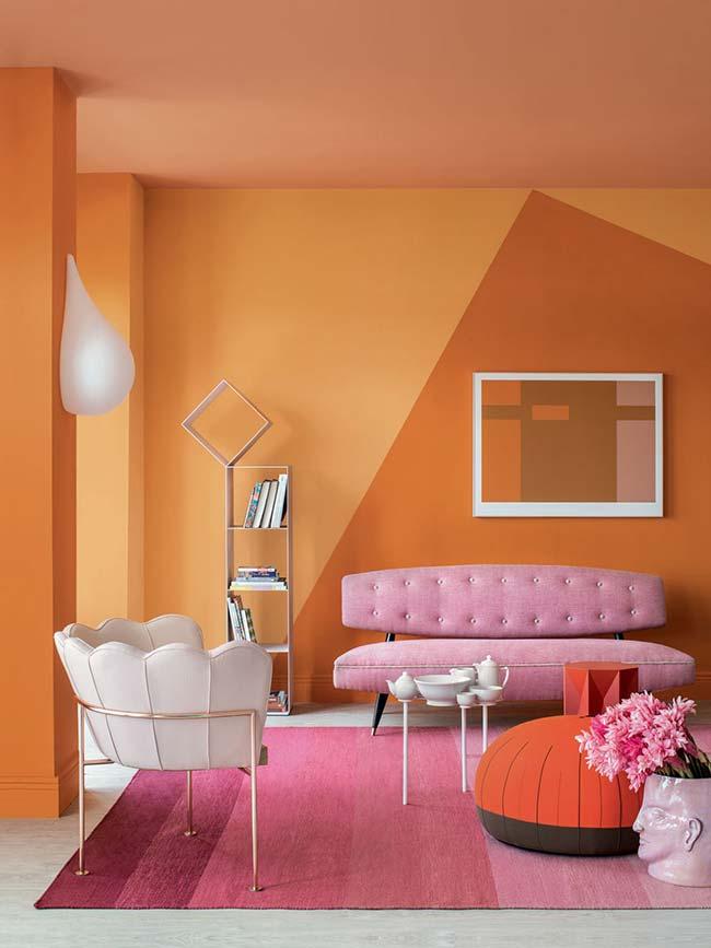 Sala pintada com diferentes tons de laranja, inclusive no teto; já a cor rosa, que pode ser considerada análoga ao laranja, foi usada em degrade no tapete e na mobília