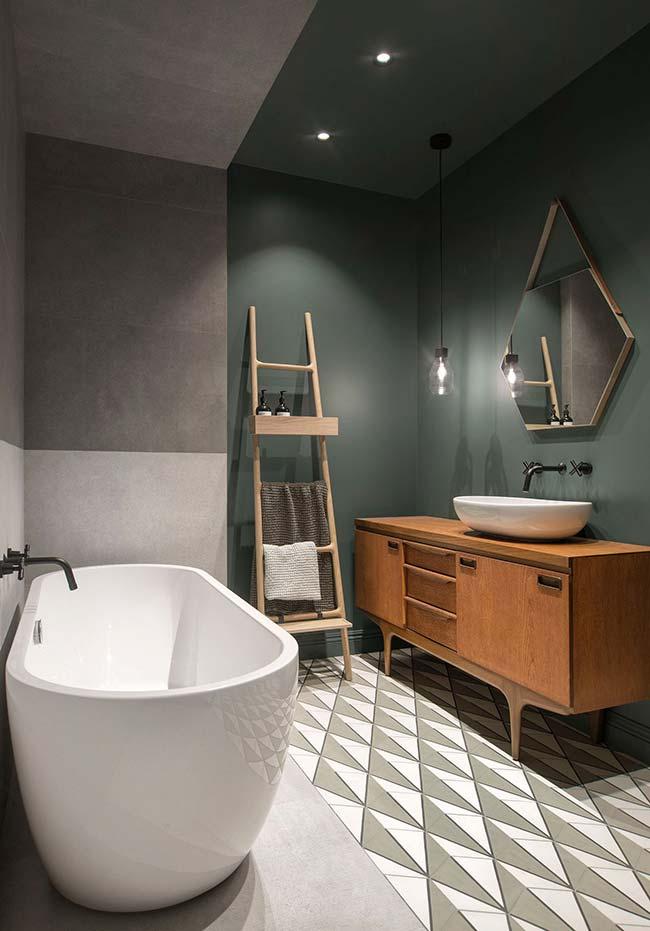 Nesse banheiro de estilo moderno, o verde bandeira da parede divide espaço com o cimento queimado