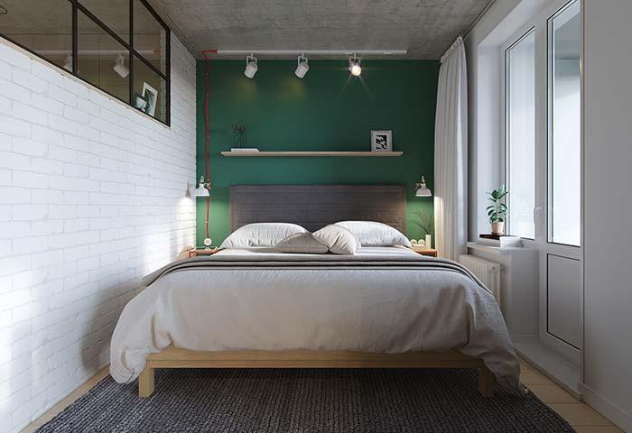 O quarto pequeno apostou no branco para as paredes laterais e no verde bandeira para a cabeceira da cama