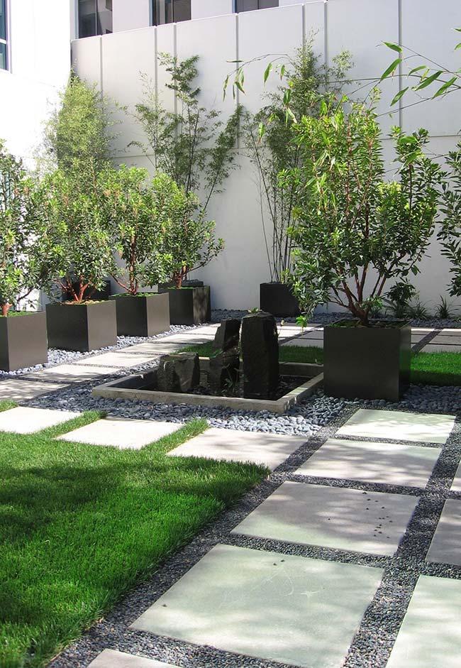 A passagem em meio ao jardim se alterna entre os pedriscos e a grama preta