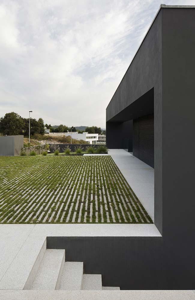 A casa moderna apostou em um quintal com grama preta intercalada a faixas de cimento