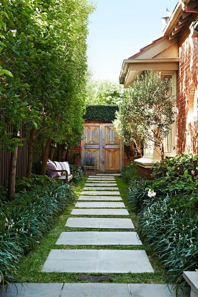 A casa rústica conta com um caminho de grama esmeralda cercada lateralmente pela grama preta