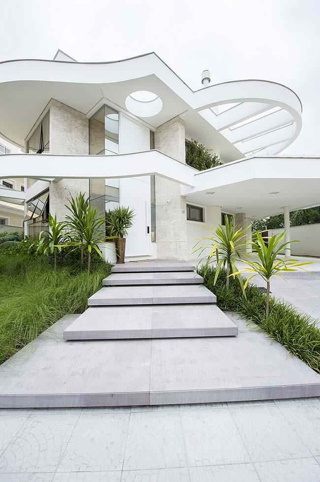Essa casa incrível, de curvas e ondas sinuosas, optou por usar a grama preta na lateral da escada