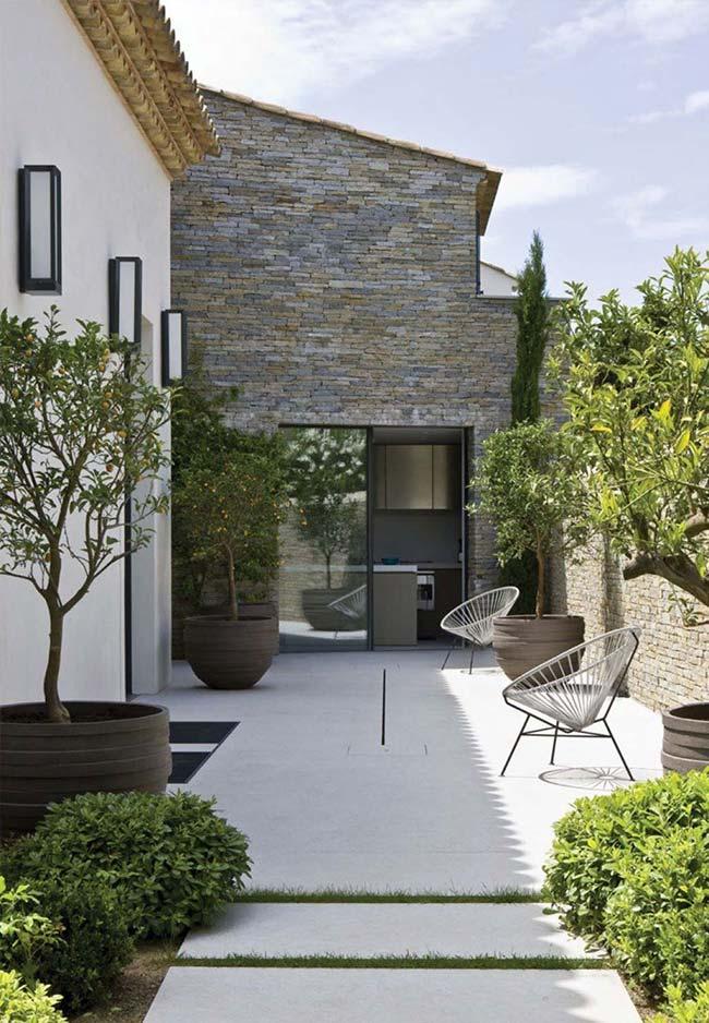 Área externa charmosa com grama preta entre o piso de concreto