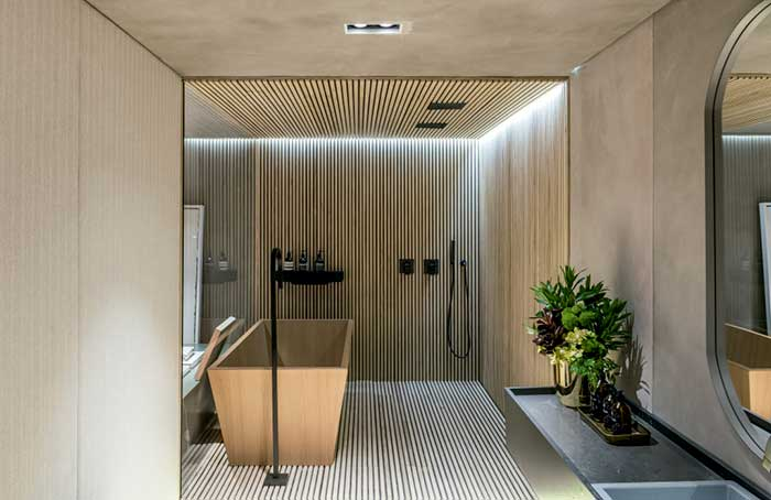 Uma caixa de ripas de madeira abraça essa área de banho