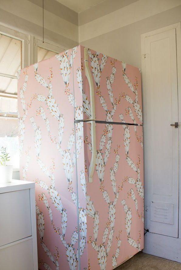 Uma geladeira envelopada com adesivo cor de rosa e estampa branca
