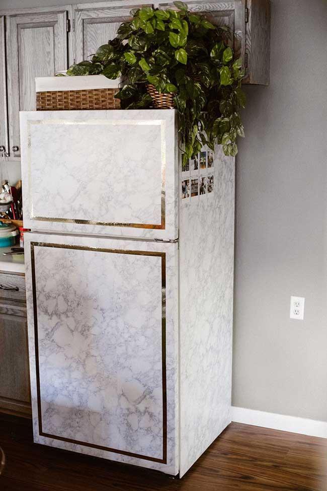 Geladeira envelopada com efeito marmorizado e fitas douradas para complementar a proposta