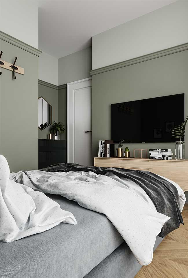 As paredes em verde musgo trazem sobriedade e um clima ameno para o quarto