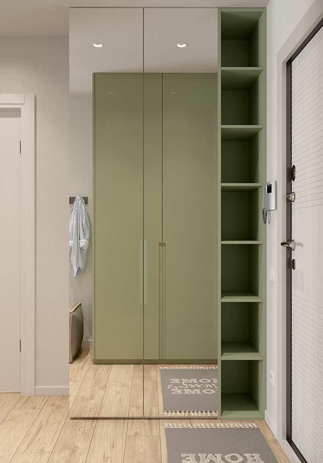 Esse hall de entrada conta com um grande armário espelhado cheio de nichos na lateral