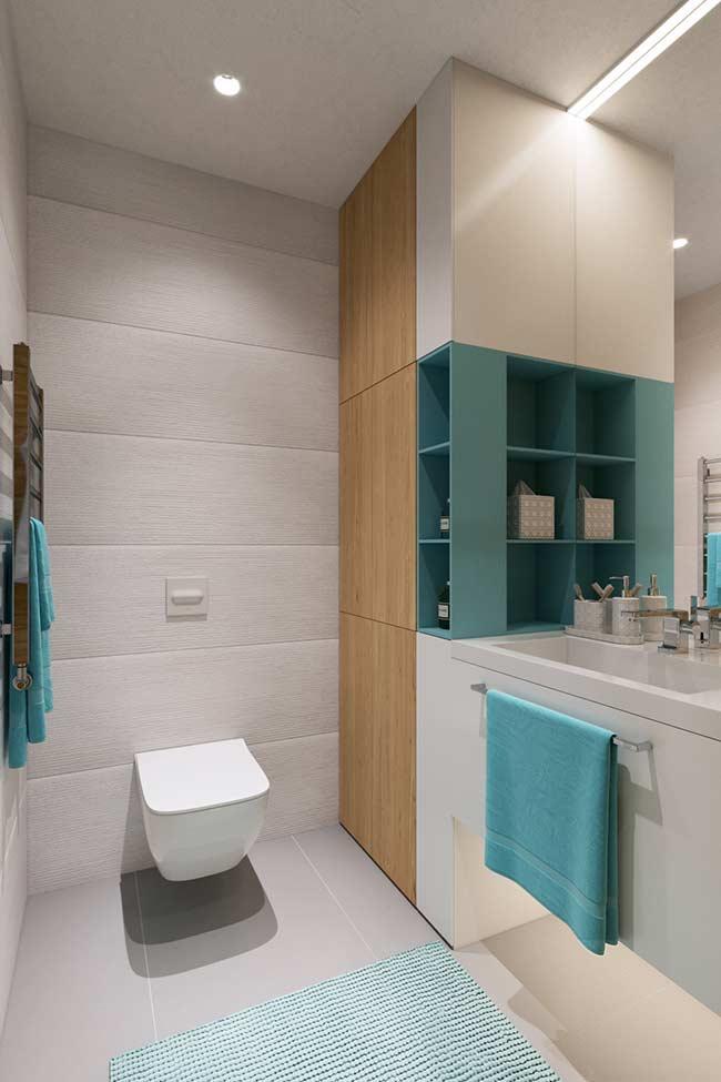O azul celeste aparece nos nichos, nas toalhas e no tapete desse banheiro