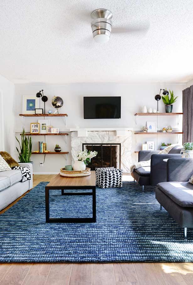 Sala branca decorada com tons sobre tons de azul, entre eles o petróleo