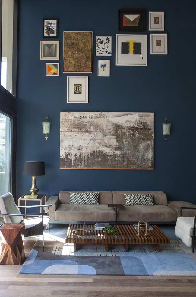 parede azul petróleo decorada com quadros dispostos de modo irregular