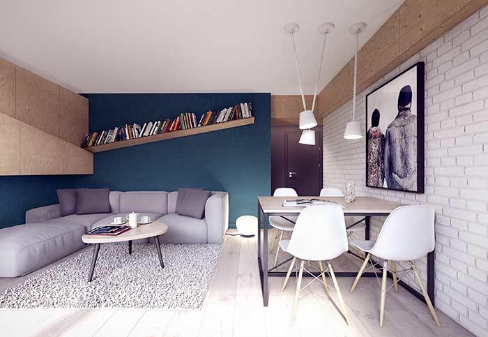 Nessa sala, o azul petróleo da parede acompanha o formato L do sofá