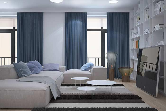 Para quebrar a brancura da sala, cortinas e almofadas azul petróleo