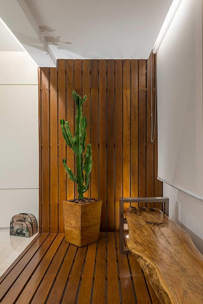 Aqui, a proposta foi revestir o chão e a parede com deck de madeira; o vaso e o banco rústico fecham a decor