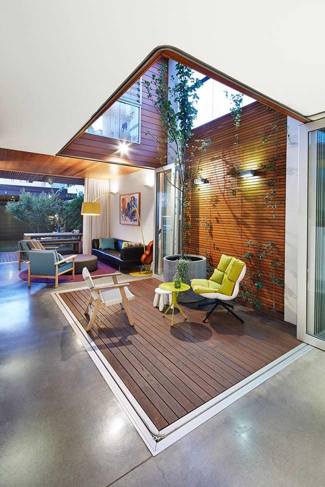 Nessa casa, a área interna ganhou um deck de madeira banhado por luz natural