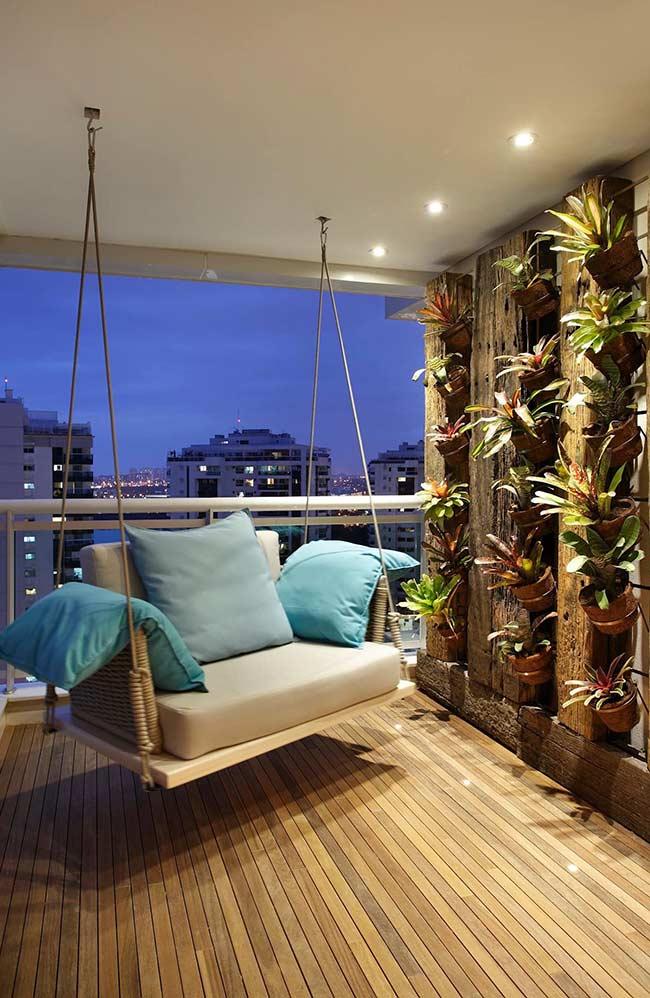 Deck de madeira, balança suspensa e jardim vertical de bromélias: