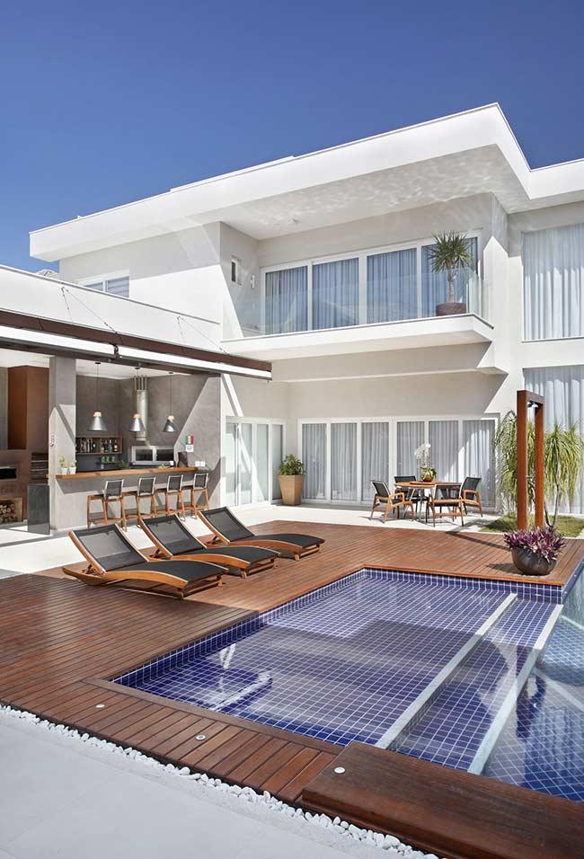 Ao invés de usar apenas o deck em torno da piscina, combine-o com pedras de quartzo branco nas laterais