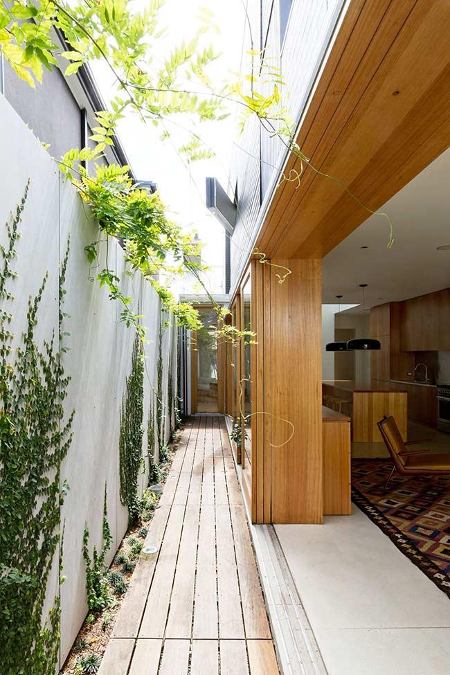 Nessa casa, o deck de madeira leva até a porta de entrada; repare que os arcos das portas também são de madeira