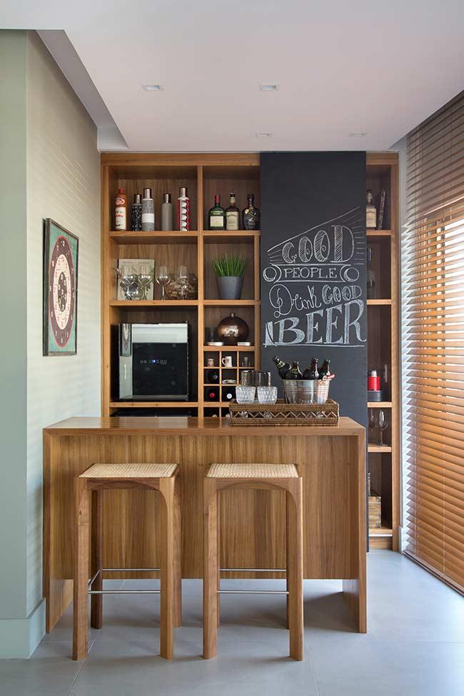 Bar todo em madeira com nichos, balcão e banquetas; o adesivo lousa deixa o ambiente despojado e divertido