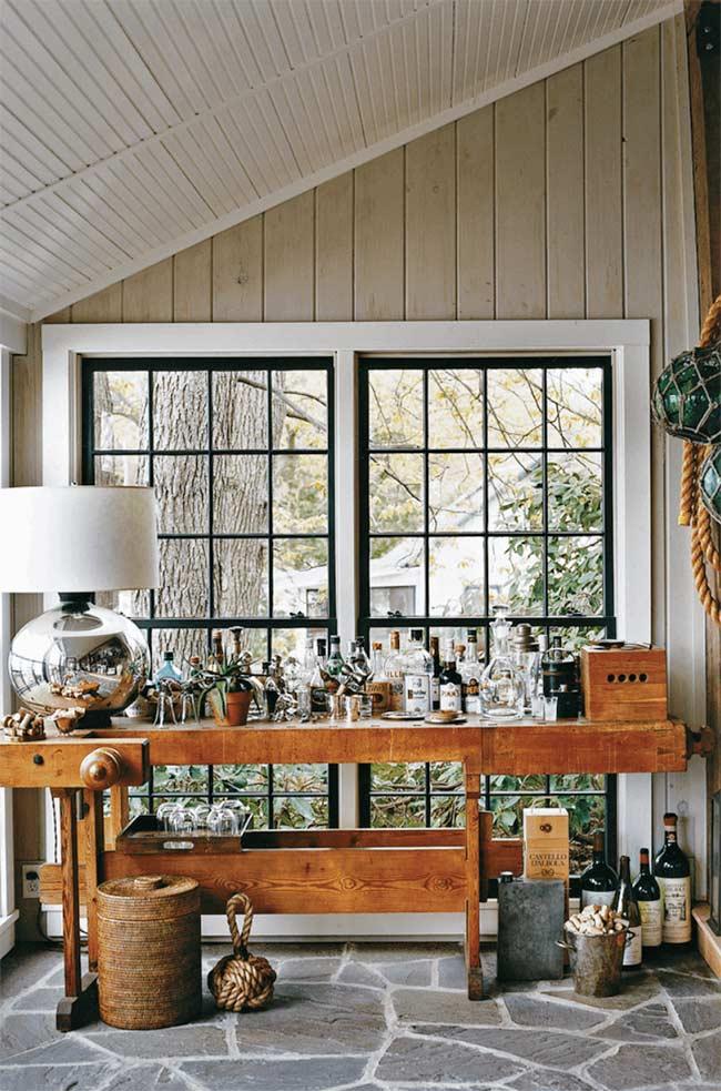 Esse bar rústico, montado à frente da janela, se destaca pela extensão da mesa em que está apoiado