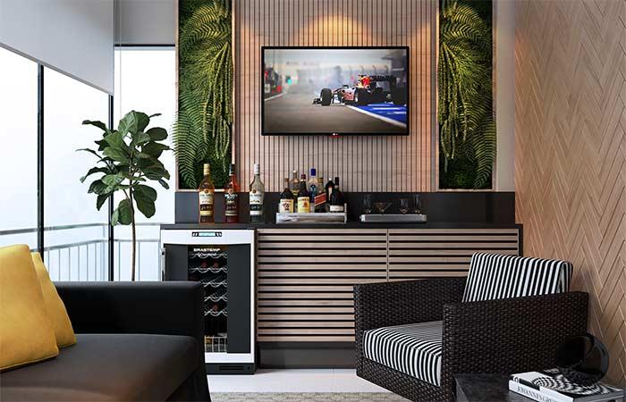 A sala de estar na varanda traz um modelo de bar integrado ao rack
