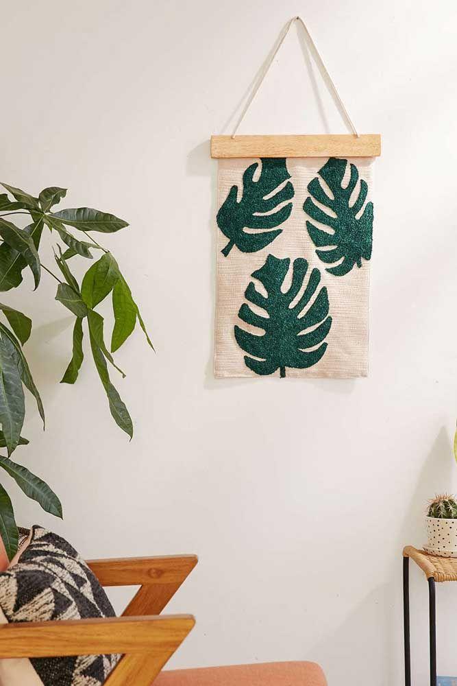 Tecido de cor crua pendurado na parede recebeu muito bem o tom vibrante de verde das folhas da Costela de Adão