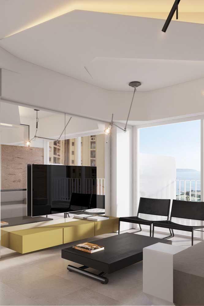 Decoração clean e moderna dessa sala usou o espelho como painel para TV