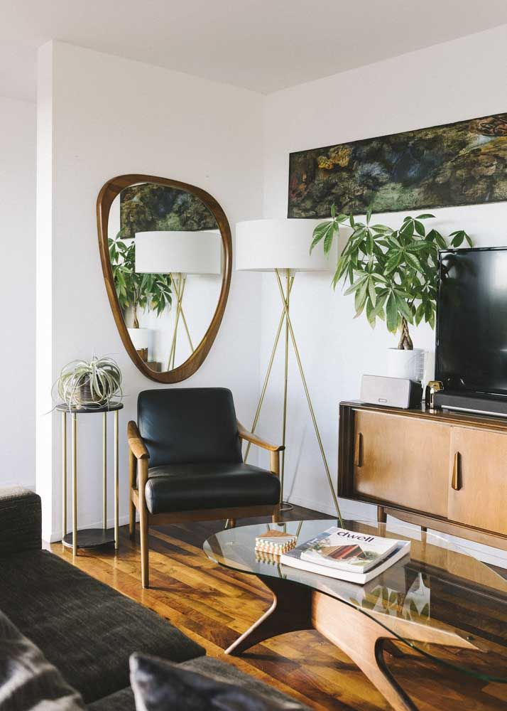 A sala de decoração clássica optou por trazer um espelho de formato irregular para quebrar a sobriedade