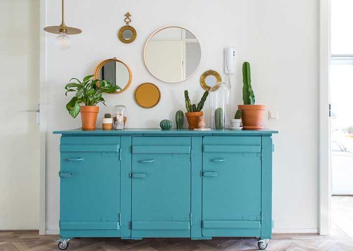 O balcão azul turquesa decorado com cactos ficou ainda mais divertido com os espelhos variados pendurados sobre ele.