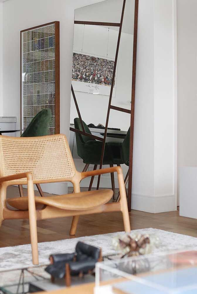 O espelho que cobre toda a altura da parede reflete a mesa de jantar à sua frente e a devolve duplicada ao ambiente
