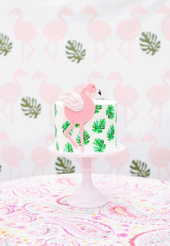 Bolo com decoração estampada de folhas e um flamingo de papel