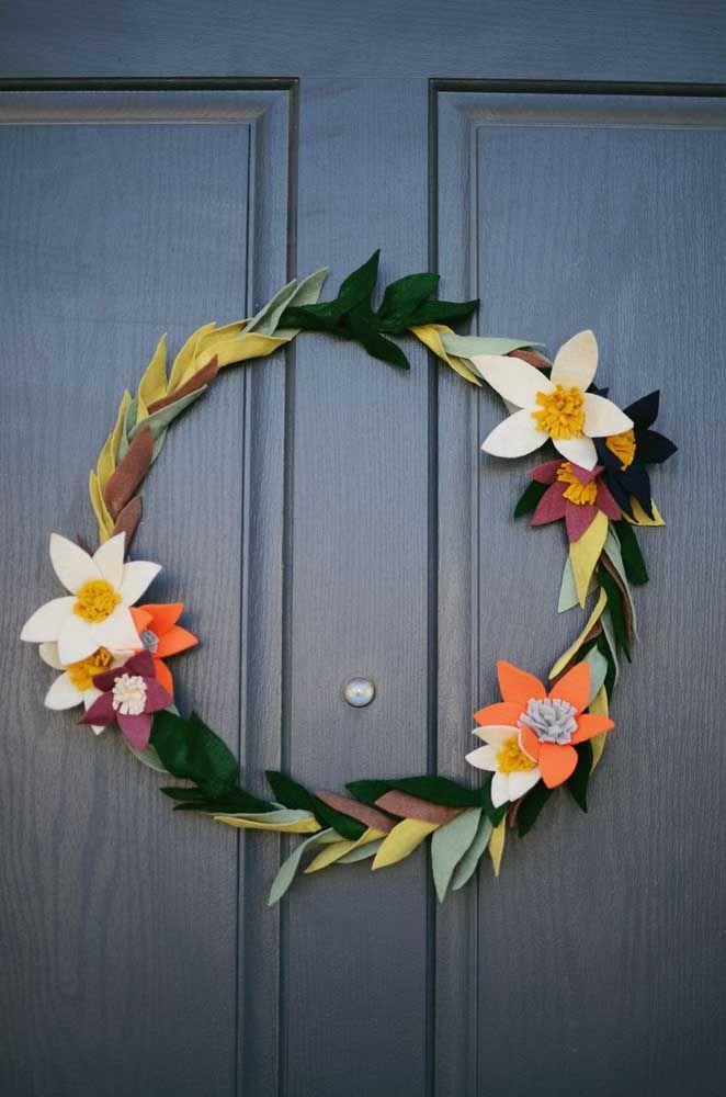 Uma guirlanda simples, colorida e delicada de folhas e flores contrastada pelo azul escuro da porta