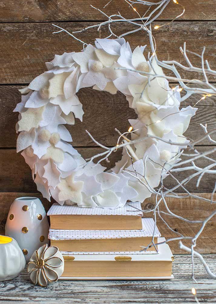 Uma guirlanda de feltro de folhas brancas para decorar o móvel de madeira escura