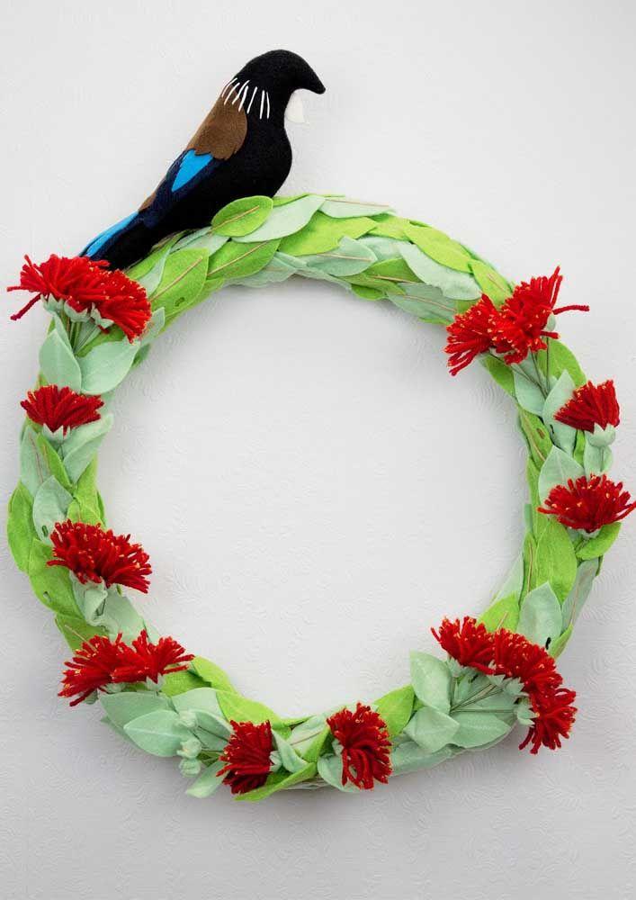Folhas verdes, flores vermelhas e um belo pássaro para coroar a guirlanda da porta